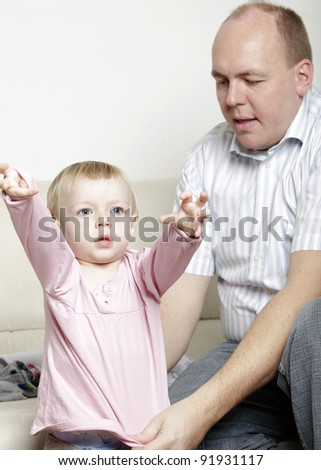 Father helping his baby daughter dress
