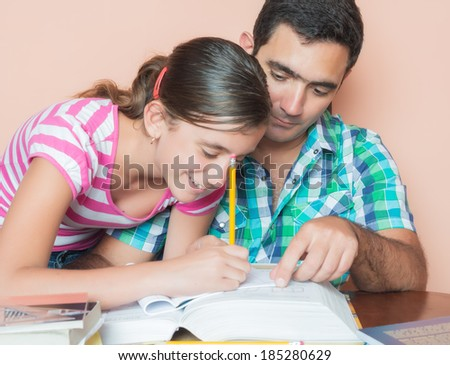 Father helping his daughter with her school homework - stock photo