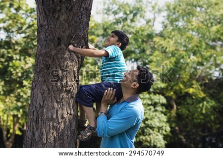 Father helping his son climb a tree - stock photo