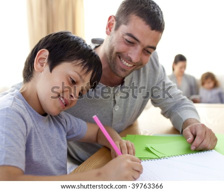 Father helping his son doing homework at home - stock photo