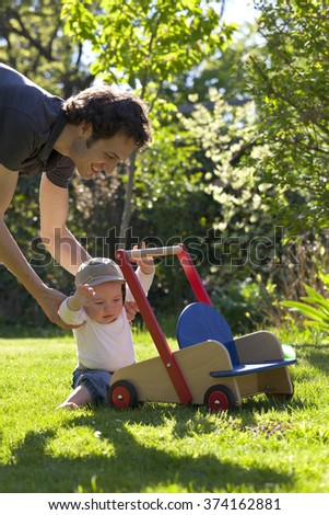 Father helping his son in garden to take his first step of life - stock photo