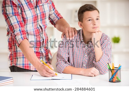 Father helping his son to do homework at home. - stock photo