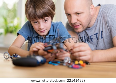 Father helping his young son build a model toy as they lean over a table together peering at the pieces - stock photo