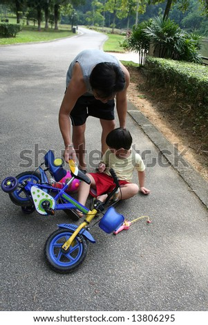 Father helping son getting up from falling off bicycle - stock photo