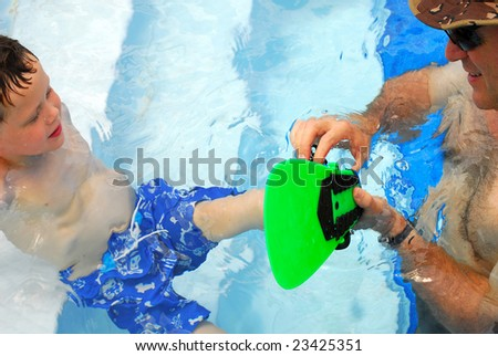 Father helping son put on swim fin in pool