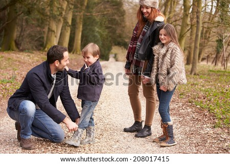 Father Helping Son To Put On Shoe During Family Walk - stock photo