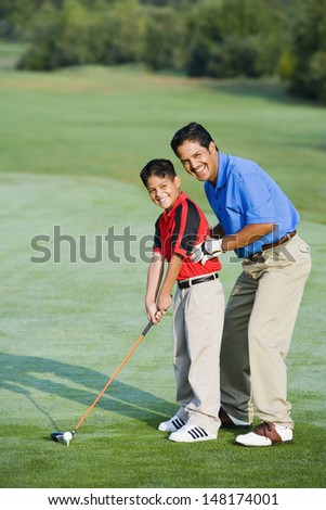 Father helping son with playing golf - stock photo