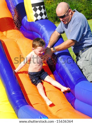 Father helping young son on water slide - stock photo