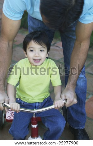Father helping young son ride tricycle - stock photo