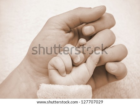Father hold baby hand in the palm - stock photo