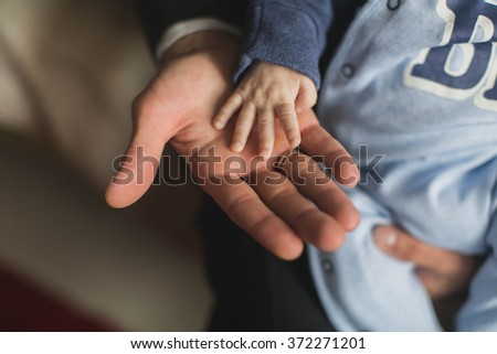 father holding baby hand - stock photo