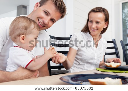 Father holding child while mother giving piece of bread to the child - stock photo