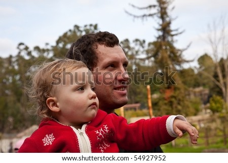 Father holding cute caucasian baby girl while walking in the park. - stock photo