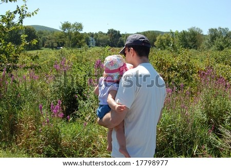 Father holding daughter in colorful meadow - stock photo