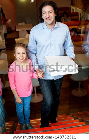 Father holding daughters hand and pizza boxes