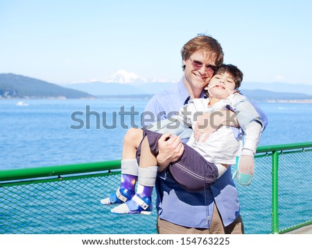 Father holding disabled son in arms on deck of ferry boat. Puget Sound in background. Child has cerebral palsy. - stock photo