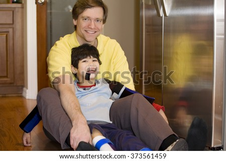 Father holding disabled son on kitchen floor. Son has cerebral palsy. - stock photo