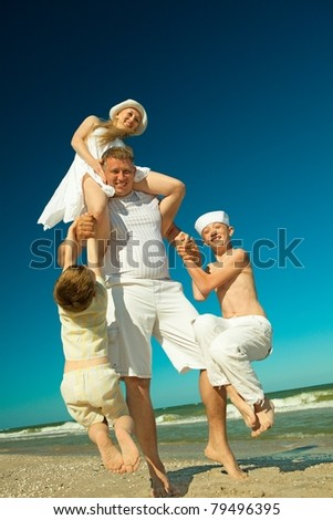 Father holding  family on beach while on vacation - stock photo