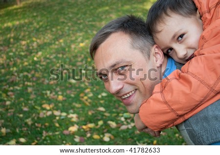 father holding grandson on his back
