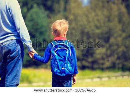 father holding hand of little son with backpack outdoors, back to school