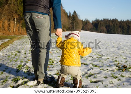 Father holding hands of his baby making first steps in the snow
