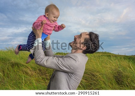 Father holding his baby daughter high in the air - stock photo