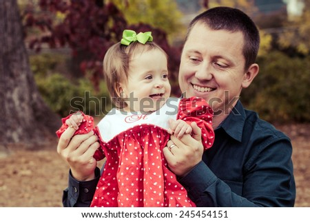 Father holding his baby girl outdoors at park during autumn in filtered image  - stock photo