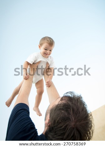 Father holding his baby son in air on legs - stock photo