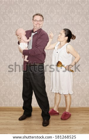 Father holding his Crying Baby and being Scalded by his Angry Wife - stock photo