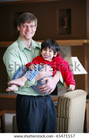 Father holding his disabled three year old son - stock photo