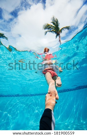 Father holding his little daughter feet while she swims in pool - stock photo