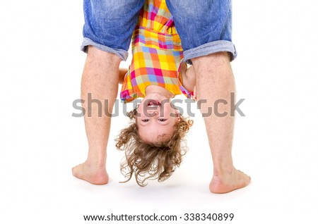 Father holding his little daughter upside down. Trust concept. - stock photo