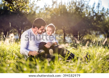 Father holding his little son, sitting on the grass