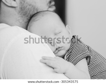 Father holding his newborn baby, black and white - stock photo