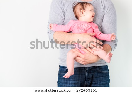 Father holding his smiling daughter. Baby is wearing pink body suit and looking at right side - stock photo