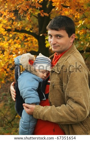 father holding his son in baby carrier - stock photo