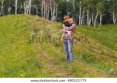 Father holding his son in his arms. Family holiday in nature. Nature, meadow on a hill near the forest.