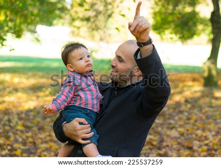 Father holding his son in the autumn season - stock photo