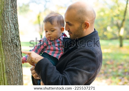 Father holding his son in the autumn season