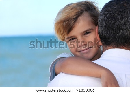 father holding his son on the beach - stock photo
