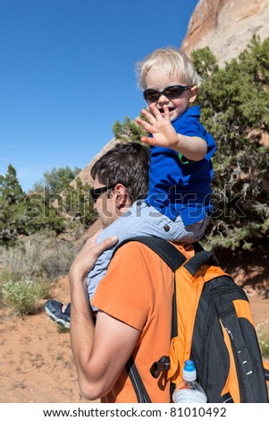 father holding his son on the shoulders hiking - stock photo