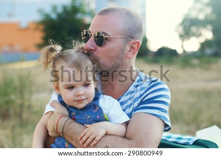 Father holding his young daughter. Outdoor session. - stock photo