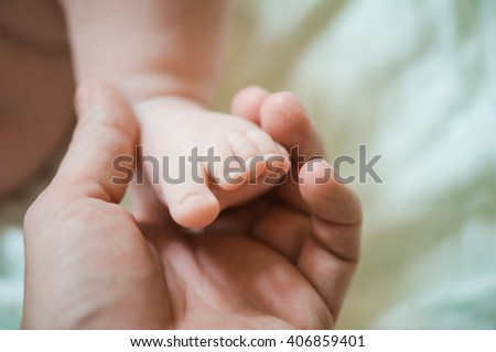 father holding newborn feet
