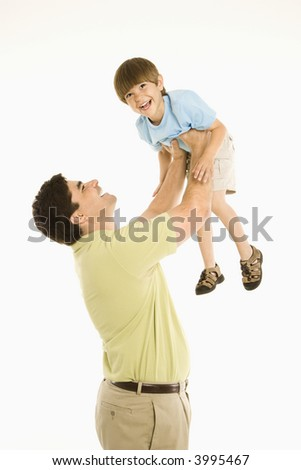 Father holding smiling son up overhead against white background. - stock photo