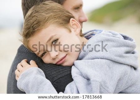 Father holding son at beach - stock photo