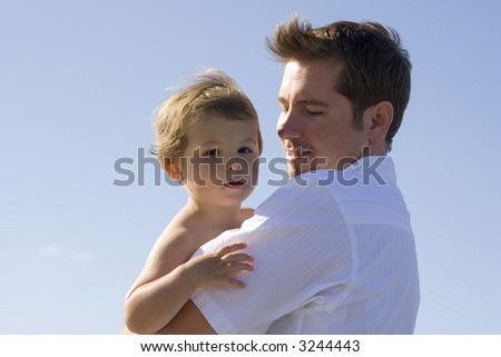 Father holding son.  Blue sky in the background. - stock photo