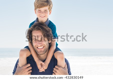 Father holding son on shoulder. Portrait of happy father and son smiling and looking at camera. Father giving his son piggyback at beach. - stock photo