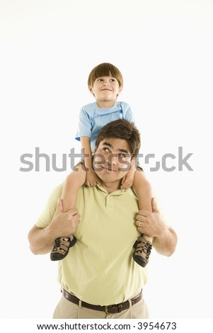 Father holding son on shoulders standing against white background. - stock photo