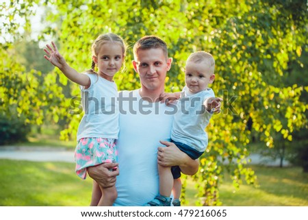 Father holding two children in her arms in the park