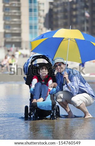 Father holding umbrella over disabled son in wheelchair at the beach - stock photo
